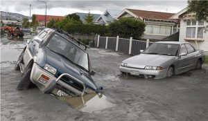 Forget about setting the parking brake; these cars are going nowhere. Christchurch neighborhoods like this one became unrecognizable due to massive liquefaction in 2011. As the water drains after the quake, the slurry congeals into cement, making its removal difficult and expensive. Photo courtesy of Stuff.co.nz