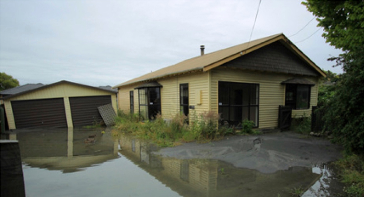 When liquefaction occurs, structures such as this Christchurch garage can sink and tilt. Photo courtesy of Becker Fraser Photos.