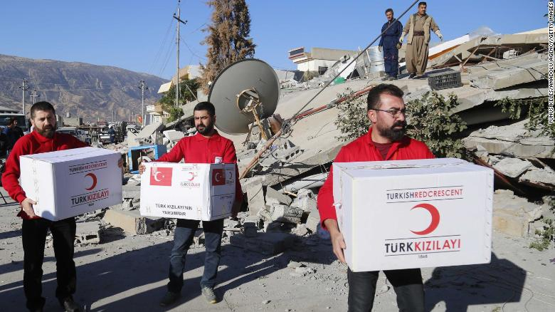 SULAYMANIYAH, IRAQ - NOVEMBER 13: Members of the Turkish Red Crescent, who reached the region as a first response, dispatch aid goods and food to the survivors of the earthquake in Derbendihan district of Sulaymaniyah, Iraq on November 13, 2017 following a 7.3 magnitude earthquake that hit the Iraq and Iran. Turkish paramedic teams and rescue teams dispatched to the disaster area under the coordination of Turkish aid agencies; AFAD (Turkey's Disaster Management Agency) and Kizilay (Turkish Red Crescent). At least 211 died and 2,504 others were injured in Iran's bordering regions, especially in Kermanshah province in west. (Photo by Yunus Keles/Anadolu Agency/Getty Images)