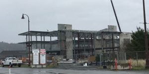 """The OSU Marine Science building under construction, April 2019. It's on a sandbar at sea level in Newport, Ore., and can be overtopped by the largest of the modeled tsunamis, as well as battered by the NOAA ships docked just to the left out of the frame. It's not often you can take the """"after"""" picture ahead of time, but this is what it may look like after being destroyed by the next tsunami. Credit: Chris Goldfinger."""