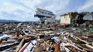 A sightseeing boat hurled onto a two-story building at Otsuchi, Iwate prefecture, by the 2011 Tohoku tsunami. This means that the tsunami barrier, visible at left, was overtopped by at least 10 m (33 ft).