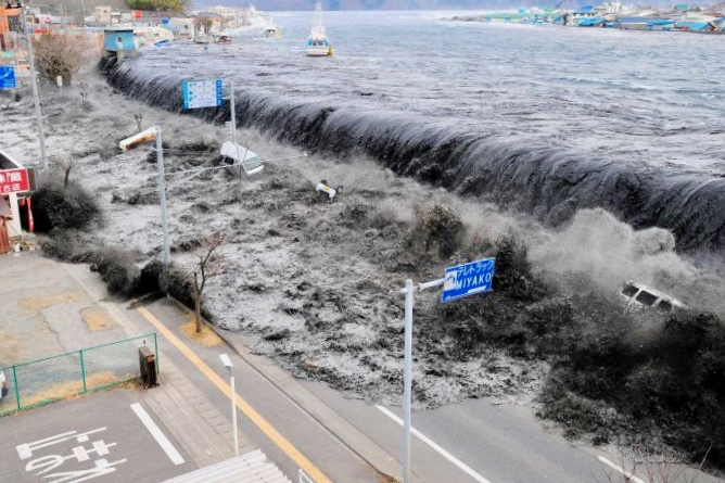 The 11 March 2011 tsunami overtops the tsunami barrier along the Tohoku coastline at Miyako, 120 km north of Sendai, Japan. Here you can see that tsunamis are not just water. They entrain massive amounts of heavy floating debris, including boats, cars, and buildings, which increase their lethal power.