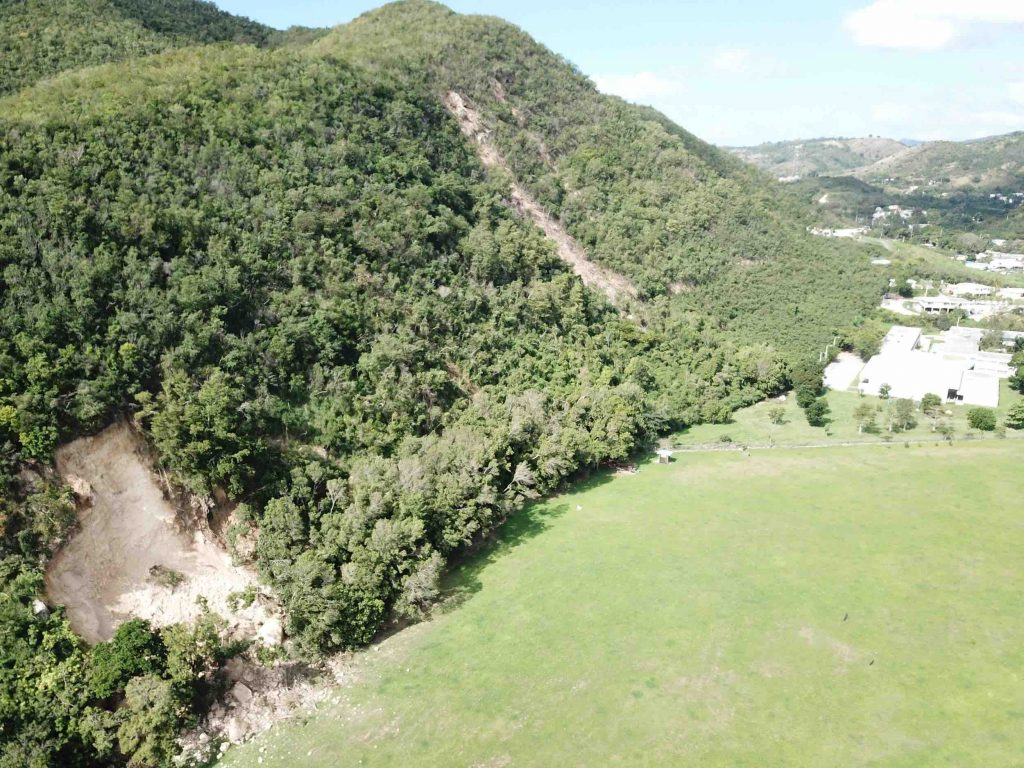 Slump in foreground. Two rock falls in the center of photo, behind Escuela Secundaria Asunción Rodríguez de Sala along road PR-127 in Guayanilla near the Río Guayanilla. Credit: Stephen Hughes