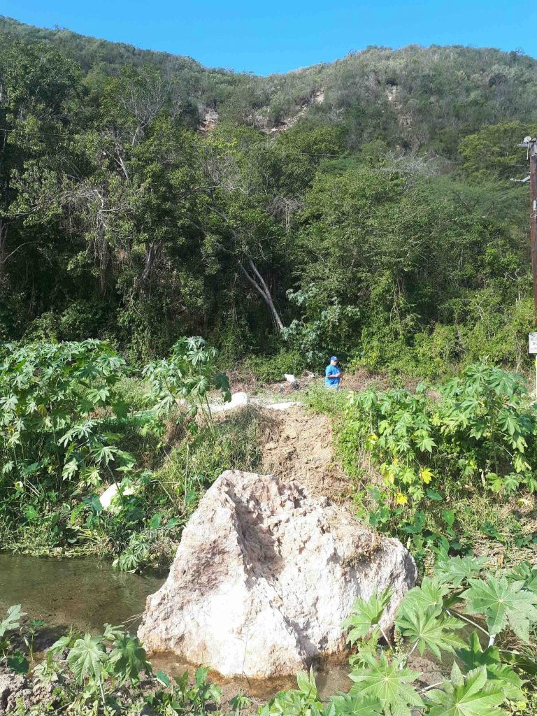 Volkswagen-sized boulder sourced from the upper part of the photo that landed in a small channel along road PR-335R in Barrio Barina of Yauco. Note multiple headscarps above, and the track of the boulder on the channel bank. Credit: Stephen Hughes