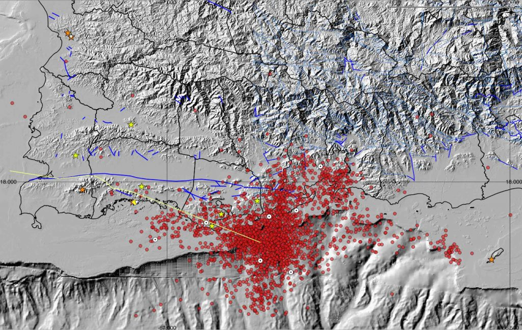 Shaded relief map of southwestern Puerto Rico showing all seismic events processed by the Puerto Rico Seismic Network between Dec. 28, 2019 and Jan. 22, 2020. A total of 2,320 events are represented as red circles. White circles with black dot in the center correspond to the most significant events in the sequence, which started on Dec. 28, 2019. The yellow line represents an estimated location of the Punta Montalva left-lateral strike-slip fault, which is thought to have an offshore extension responsible for the seismic activity. Stars represent seismic or geodetic stations. A noticeable NW and NNE spatial distribution of the events may represent faults responsible for the current seismic activity.