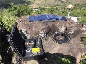 Campaign-style GPS equipment deployed to GPS control points in the vicinity of the epicentral region. Data will be compared to predicted offsets to validate the focal mechanisms obtained by seismic sources. GPS antenna (on the right) is mounted on a 0.5 meter spike mount and receiver (inside black box on the left) is powered by a 12 volt battery with solar panel support. Re-occupation of each site lasts between 3 days to one week. Credit: Alberto López