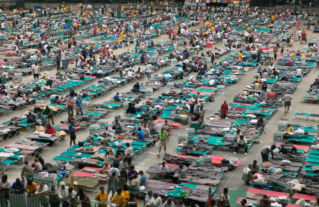 Hurricane Katrina survivors shelter at the Houston Astrodome after being evacuated from New Orleans in 2005. Disasters like Katrina reveal the differences between people with means and those without, and affect the classes differently. Pandemics like the coronavirus also affect the classes differently and disproportionately. Credit: Andrea Booher/FEMA