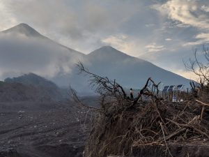 Fuego (left) and Acatenango (right) volcanoes tower over the new seismic and infrasound monitoring site at La Reunion Golf Course in Guatemala. The golf course was impacted by pyroclastic flows on June 3, 2018, and has been affected by subsequent lahars. Credit: USGS
