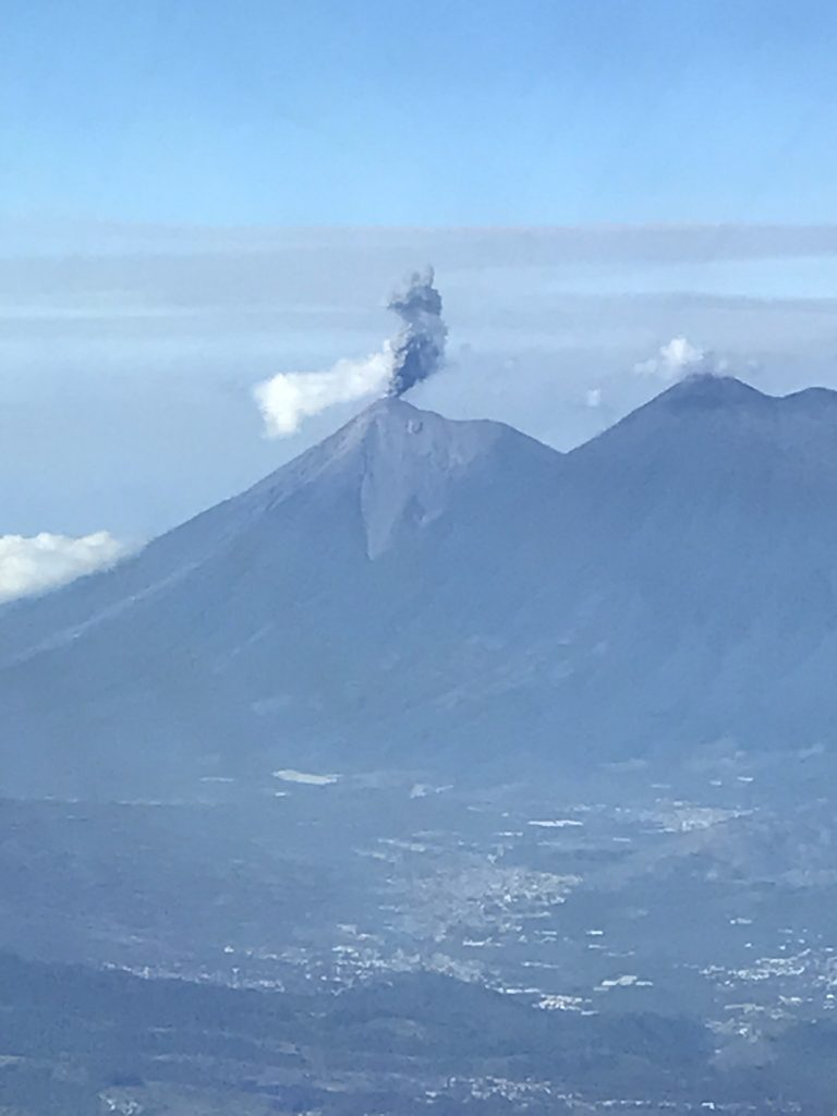 Photo of ash arising from the Guatemalan Volcán de Fuego, taken from the cockpit of a commercial airliner. Such spurts of ash are easily avoided by aviators, but if a large eruption begins suddenly, winds change, or an airplane is flying at night, these hazards become harder to see. Credit: Tom Gonzalez