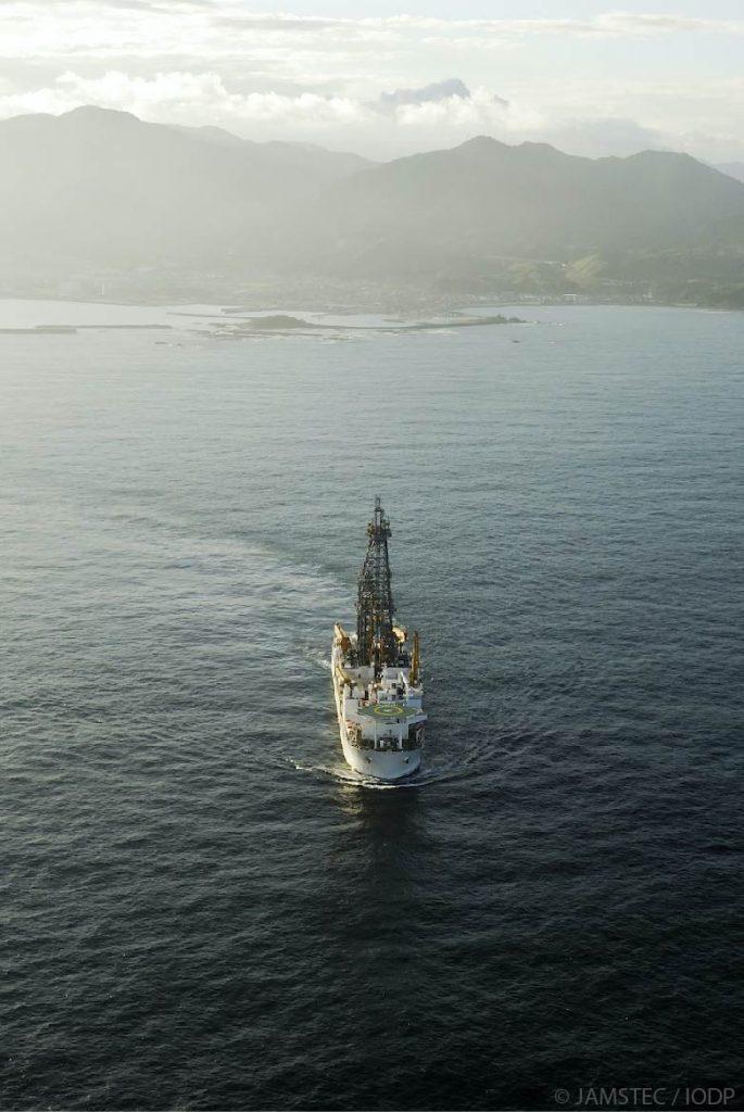 Chikyu vessel in open ocean. Mountains in background.