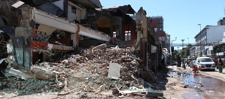 Side view of partly collapsed building surrounded by rubble