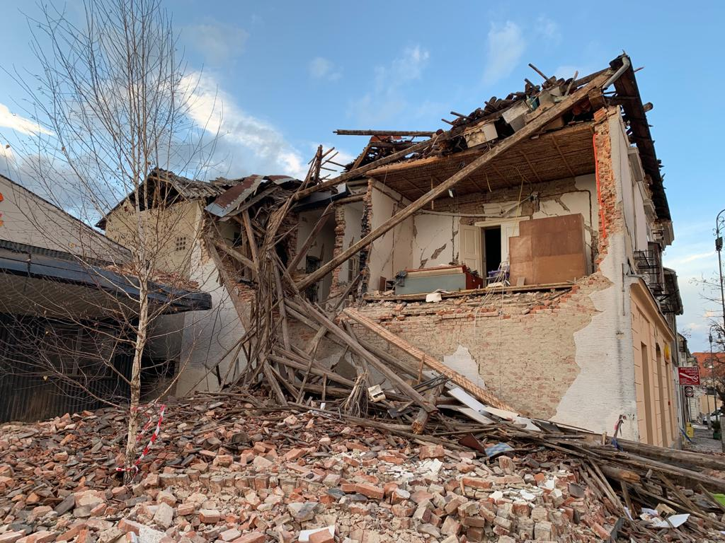 photo of a building with one wall collapsed into a pile of bricks.