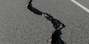 long jagged crack in roadway with people in background examining the road