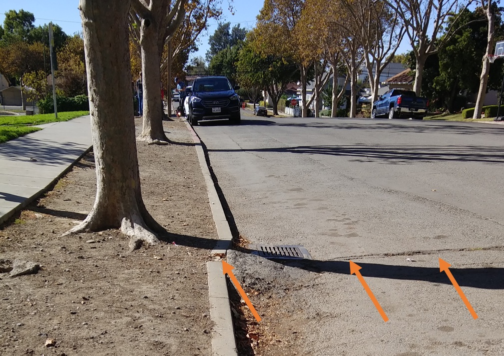 photo of road with cracks and an offset curb. Orange arrows point toward crack in road.