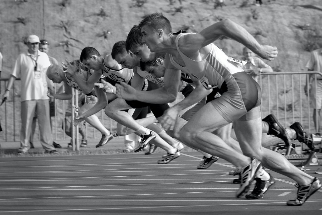 Photo of people sprinting from the starting line on a racetrack