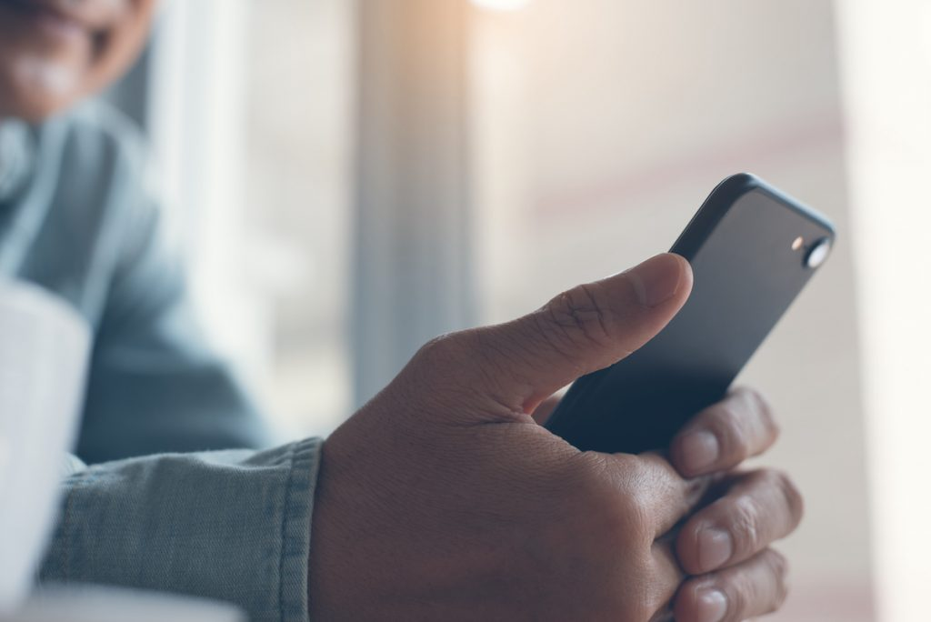 Photo d'une personne tenant un téléphone portable.