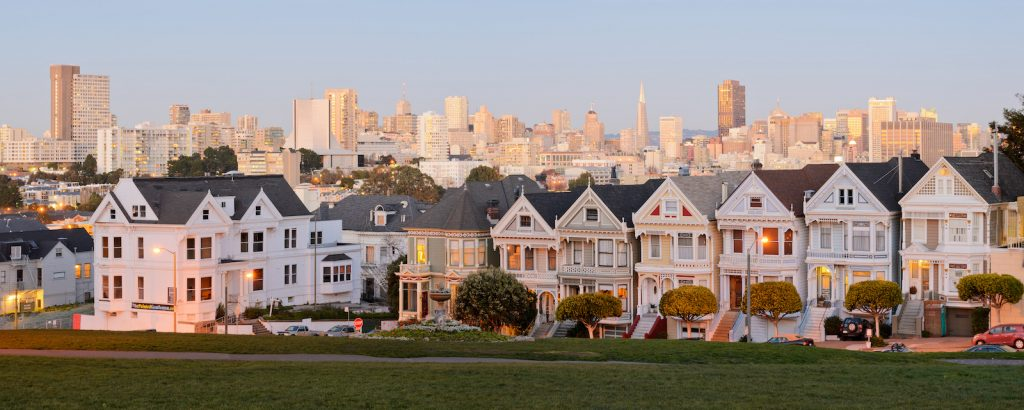 Photo of iconic San Francisco homes with cityscape in background.