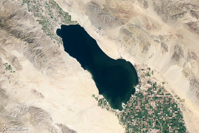 Dark green lake with agricultural land at top left and bottom right.