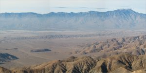 Alt text: A panoramic view of desert landscape, close-up and far-away mountains, and a valley with a visible fault in the middle.