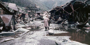 Photo of destroyed buildings along a road and a person walking