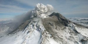 Photo of snow-covered volcano peak with cloud coming from the top