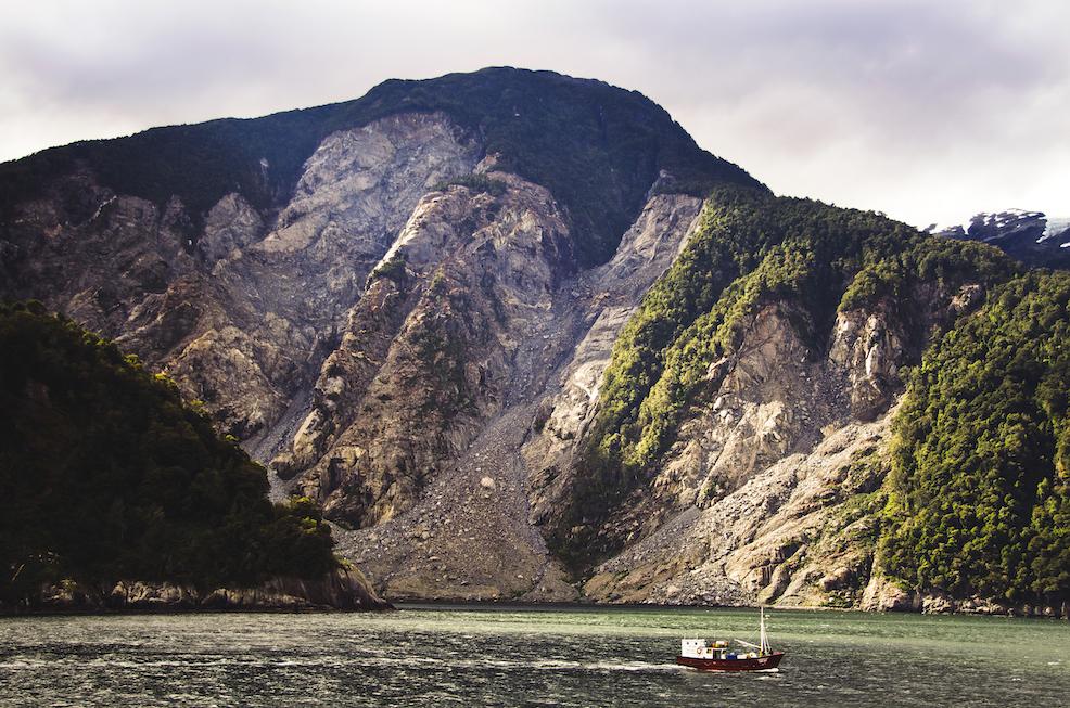 Un pequeño bote en primer plano, con un acantilado al fondo