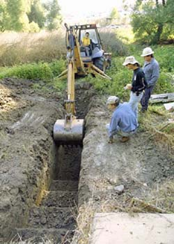 Photo of backhoe digging narrow trench as people watch