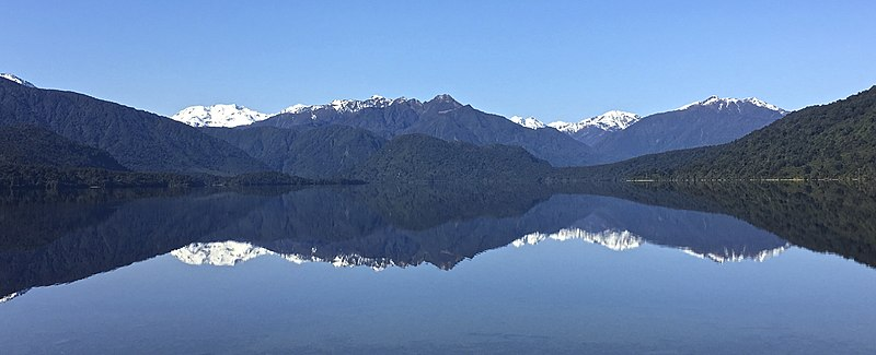 Photo of lake in foreground with reflection of mountains present in background