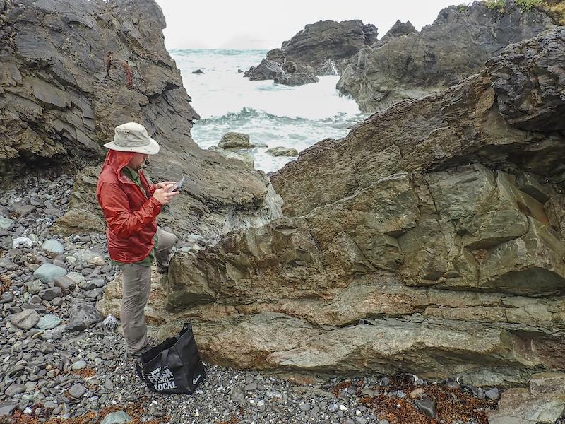 Photo of person standing next rock near a shoreline
