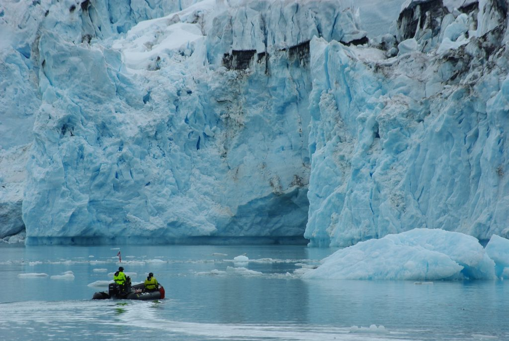 people in a small boat in front of a wall of blue ice