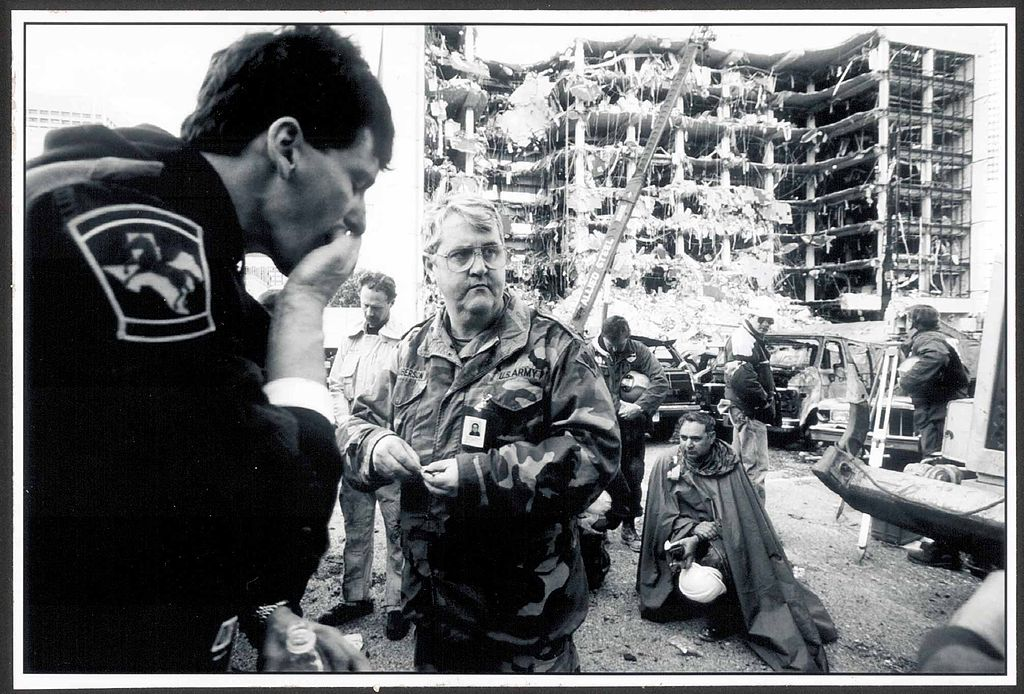 U.S. Army Chaplain Lt. Col. Roberson gives communion to search and rescue workers across the street from the Alfred P. Murrah Federal Building. A fertilizer bomb exploded, destroying a single column, after which the rest of the building crumpled in a progressive collapse. Credit: Tech. Sgt. Marvin Krause; released by U.S. Department of Defense, Public Domain