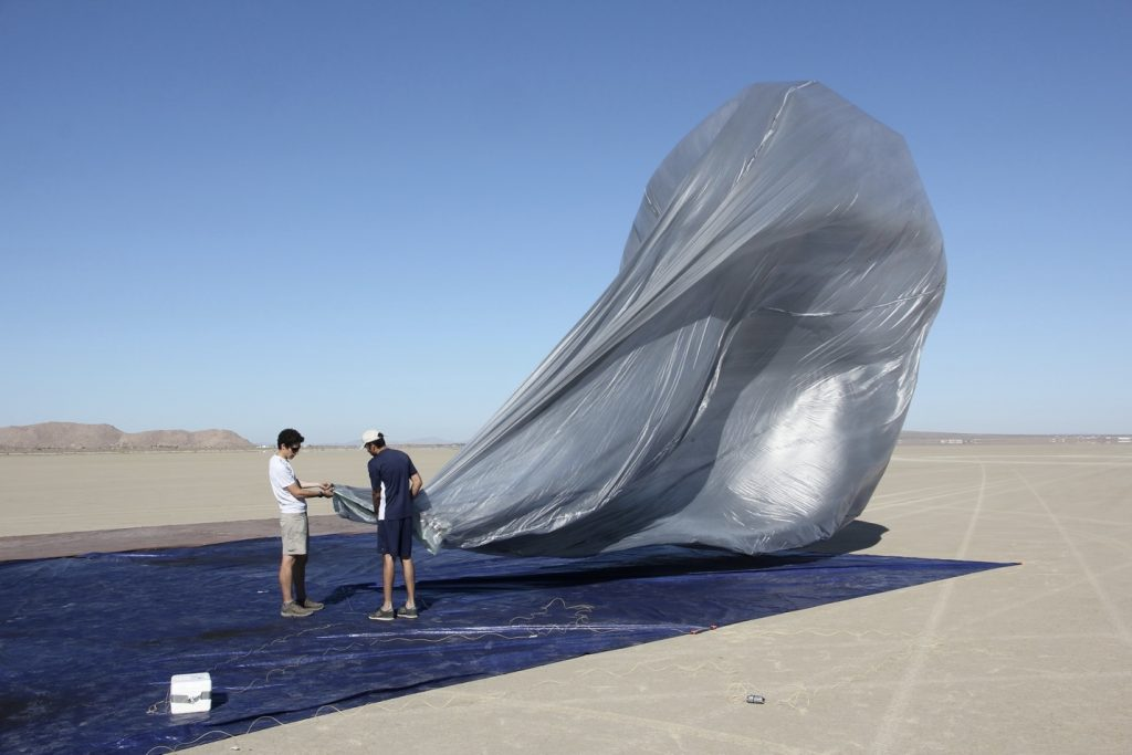 Researchers in the Mohave Desert of California prepare a high-altitude balloon with a white box, or package, containing the electronics. Credit: NASA/JPL-Caltech