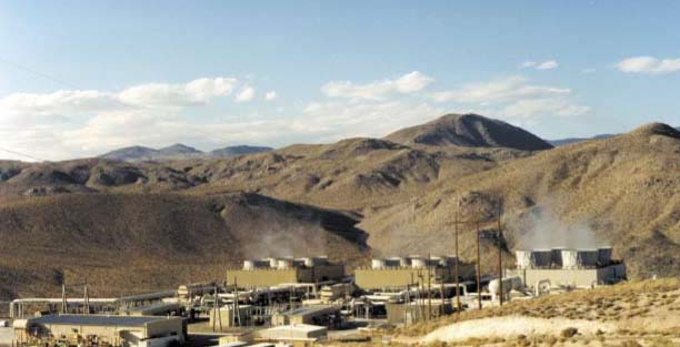 Warehouse buildings and large pipes in a hilly desert landscape.