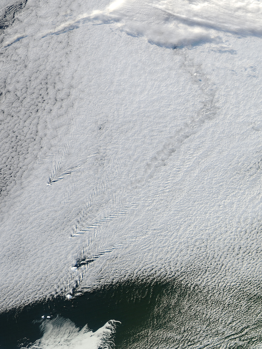 Satellite image of cloud cover with a few tiny black dots